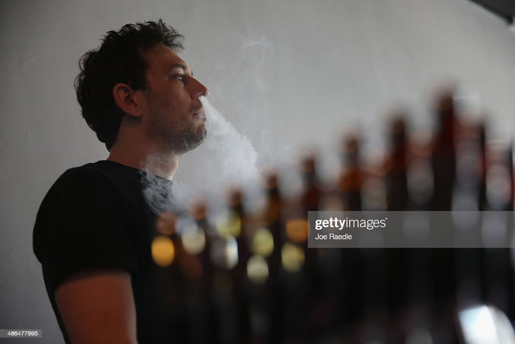Will Prusner, store manager, smokes an electronic cigarette as he helps a customer shop for an electronic cigarette at the Vapor Shark store on April 24, 2014 in Miami, Florida. Brandon Leidel, CEO, Director of Operations Vapor Shark, said he welcomes the annoucement by the Food and Drug Administration that they are proposing the first federal regulations on electronic cigarettes, which would ban sales of the popular devices to anyone under 18 and require makers to gain FDA approval for their products.
