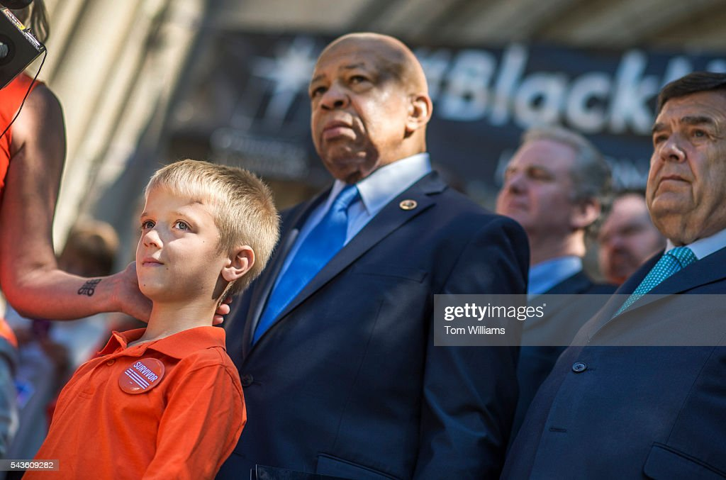 Will Ratna, 7, listens to his mother Kate, a victim of gun violence, speak during rally to call for action on gun safety measures on the steps of the Cathedral of the Incarnation in Baltimore, Md., June 29, 2016. Appearing from left are Reps. Elijah Cummings, D-Md., Chris Van Hollen, D-Md., and Dutch Ruppersberger, D-Md. Kate and her father were shot in front of Will by her then husband during a 2012 incident in Florida.