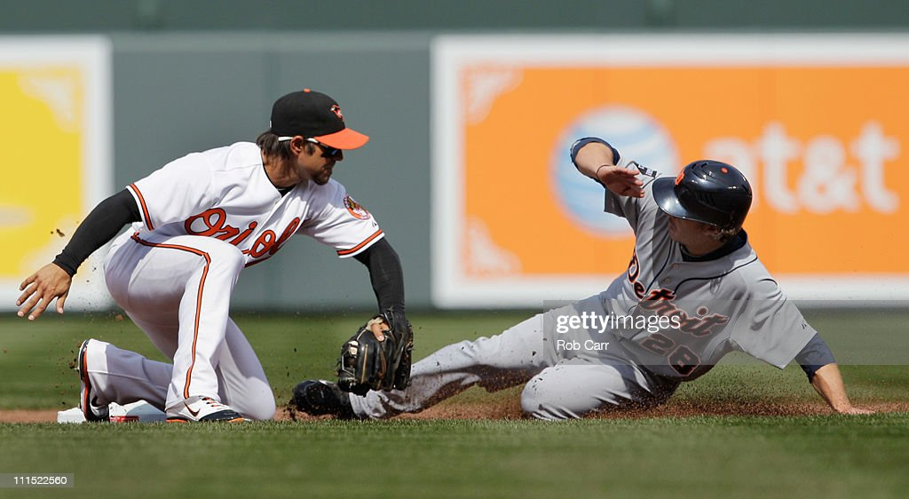 Will Rhymes #28 of the Detroit Tigers steals second base as Brian Roberts #1 of the Baltimore Orioles applies the late tag during the third inning during opening day at Oriole Park at Camden Yards on April 4, 2011 in Baltimore, Maryland.