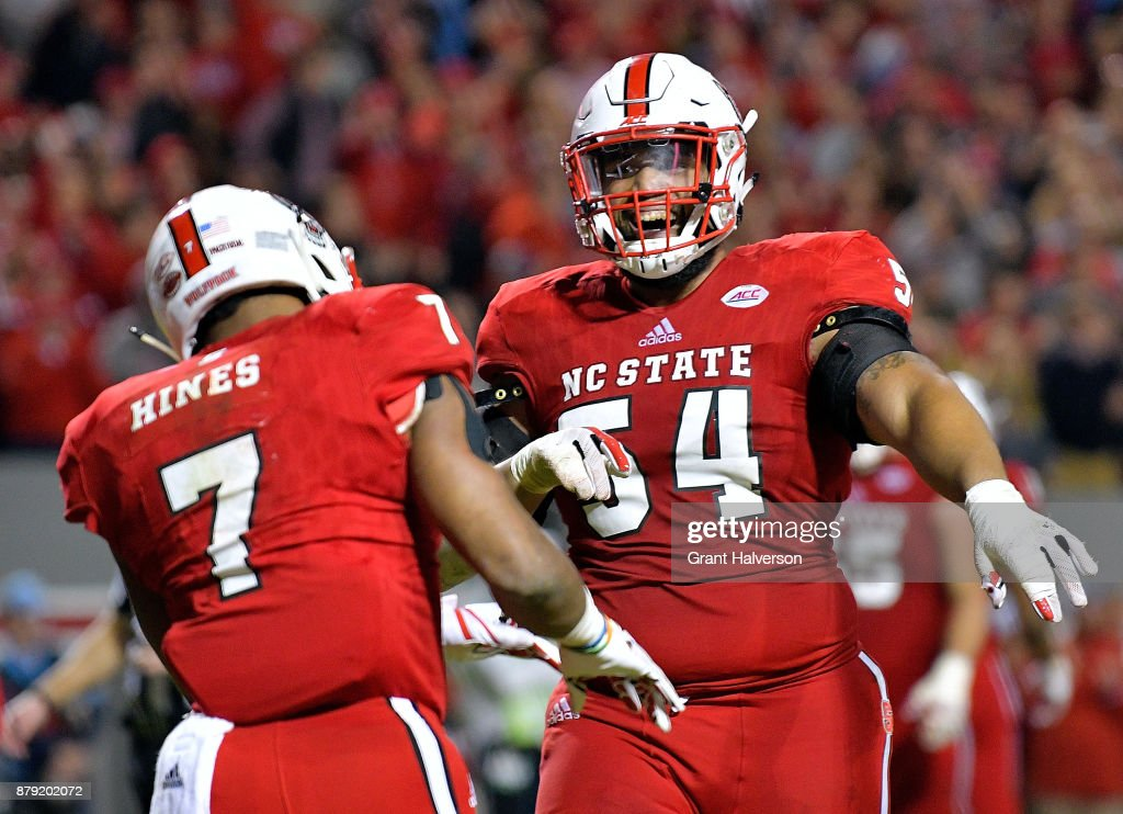 Will Richardson #54 of the North Carolina State Wolfpack celebrates with Nyheim Hines #7 of the North Carolina State Wolfpack after Hines' touchdown against the North Carolina Tar Heels during their game at Carter Finley Stadium on November 25, 2017 in Raleigh, North Carolina. North Carolina State won 33-21.