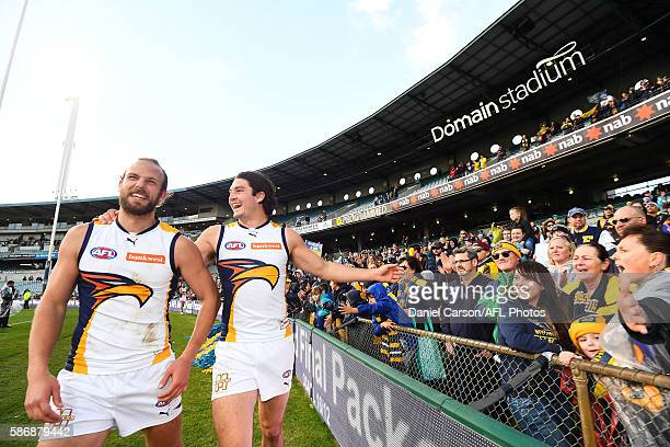 Will Schofield and Tom Barrass of the Eagles celebrate with the fans during the 2016 AFL Round 20 match between the Fremantle Dockers and the West...
