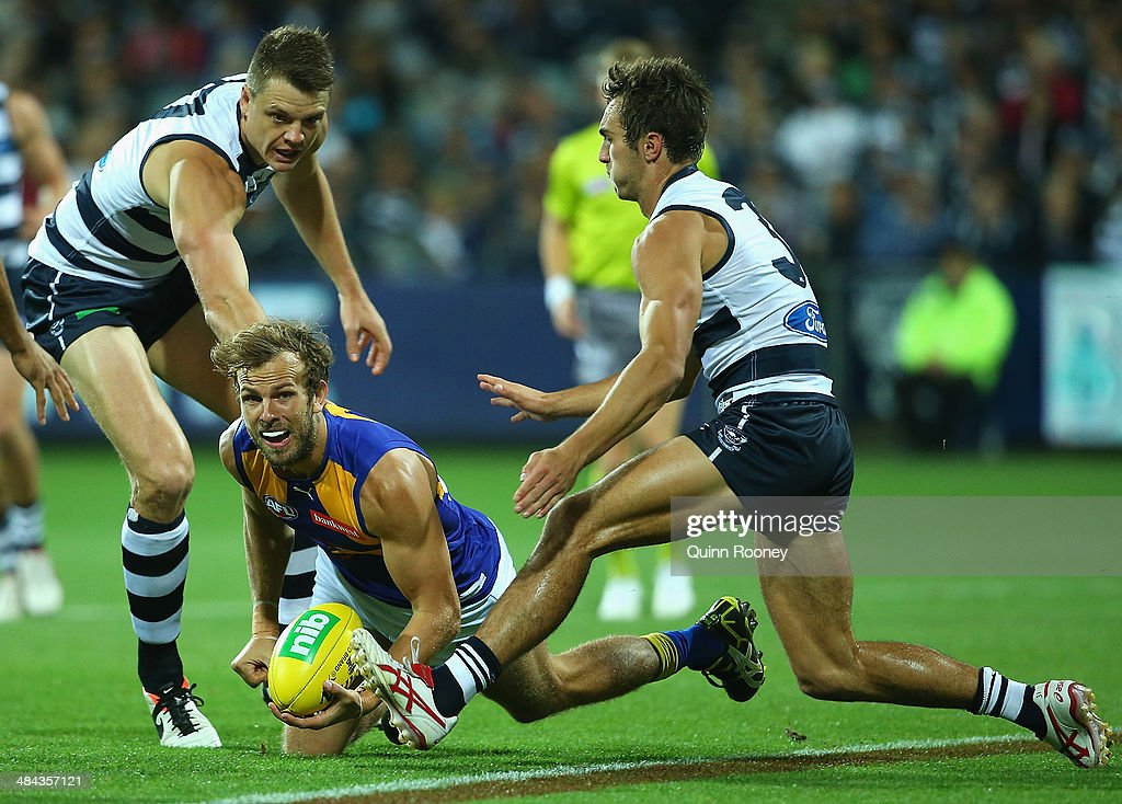 Will Schofield of the Eagles handballs whilst being tackled by <a gi-track='captionPersonalityLinkClicked' href=/galleries/search?phrase=Hamish+McIntosh&family=editorial&specificpeople=221099 ng-click='$event.stopPropagation()'>Hamish McIntosh</a> of the Cats during the round four AFL match between the Geelong Cats and the West Coast Eagles at Skilled Stadium on April 12, 2014 in Melbourne, Australia.
