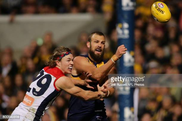 Will Schofield of the Eagles handpasses the ball under pressure from Jayden Hunt of the Demons during the round 14 AFL match between the West Coast...