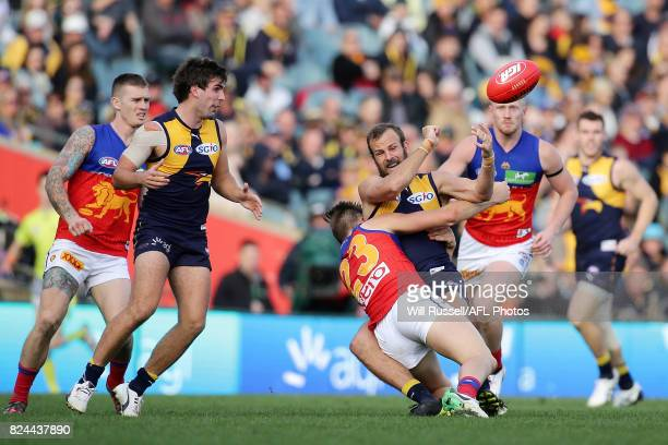 Will Schofield of the Eagles handpasses the ball under pressure from Josh Schache of the Lions during the round 19 AFL match between the West Coast...