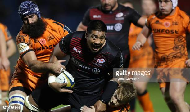 Will Skleton of Saracens ia tackled by Josh Strauss and Michael Haley of Sale Sharks during the AngloWelsh Cup match between Sale Sharks and Saracens...