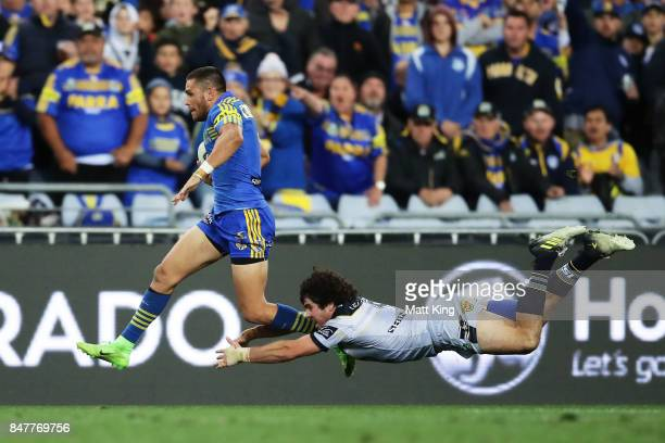 Will Smith of the Eels makes a break and beats the tackle of Jake Granville of the Cowboys to score a try during the NRL Semi Final match between the...