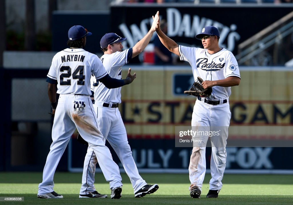 Will Venable of the San Diego Padres right Chris Denorfia center and Cameron Maybin highfive after beating the Seattle Mariners 41 in a baseball game...