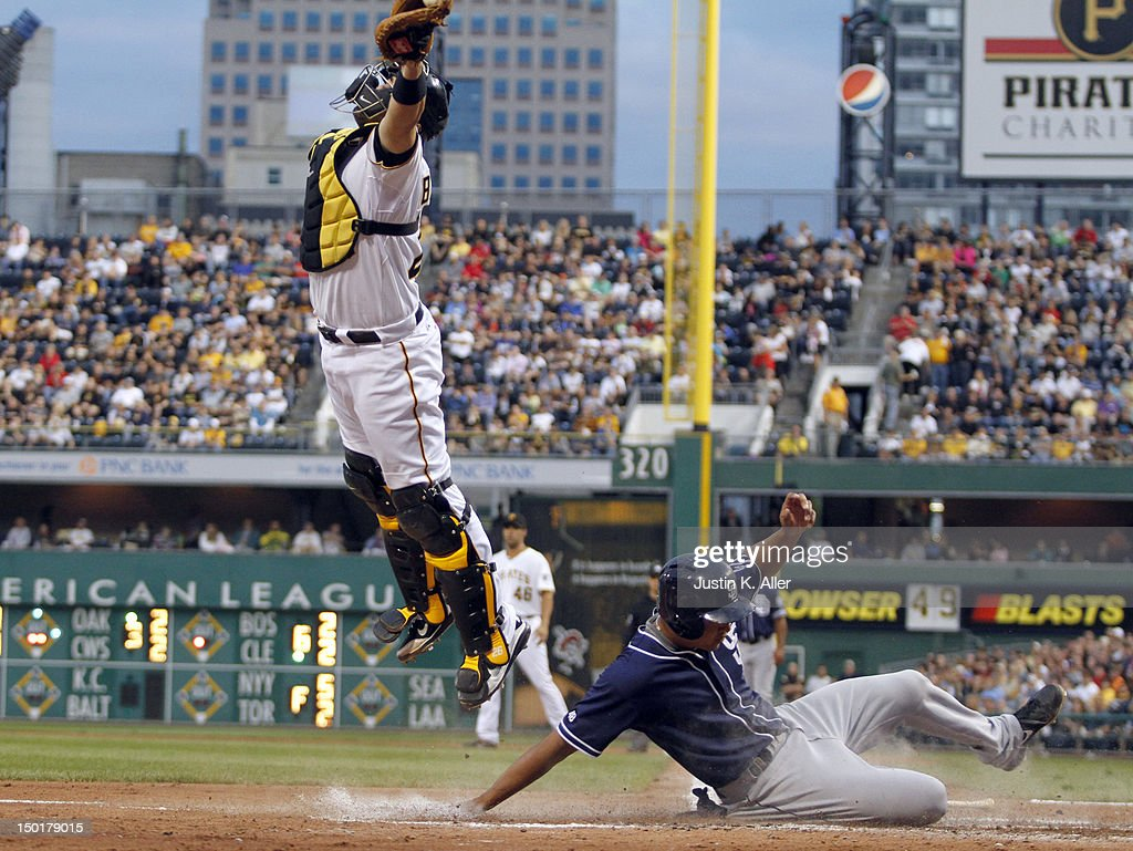 Will Venable of the San Diego Padres slides in under catcher Rod Barajas of the Pittsburgh Pirates during the game on August 11 2012 at PNC Park in...