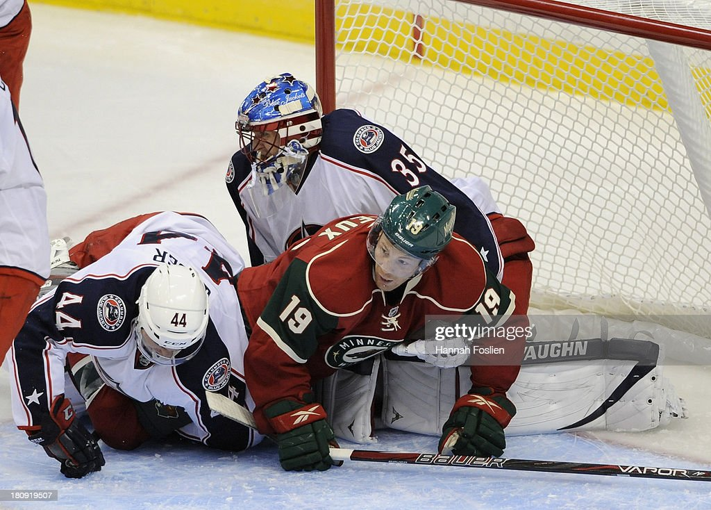 Will Weber #44 of the Columbus Blue Jackets and <a gi-track='captionPersonalityLinkClicked' href=/galleries/search?phrase=Stephane+Veilleux&family=editorial&specificpeople=217366 ng-click='$event.stopPropagation()'>Stephane Veilleux</a> #19 of the Minnesota Wild land on goaltender Jeremy Smith #35 of the Columbus Blue Jackets during the second period of the preseason game on September 17, 2013 at Xcel Energy Center in St Paul, Minnesota. The Blue Jackets defeated the Wild 3-1.