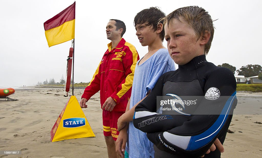 Will White and Sergio Schuler stand with Dave Litton as they look out to sea, the day after saving a mans life, on December 30, 2012 in Waikato, New Zealand. The two 12 year old boys helped a Chinese immigrant to shore after they saw him struggling in the sea.