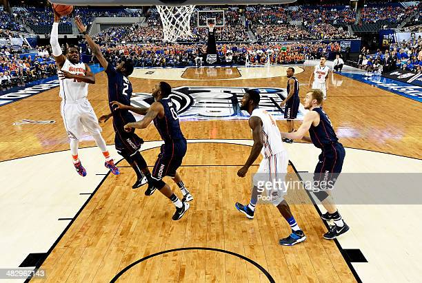 Will Yeguete of the Florida Gators goes to the basket as DeAndre Daniels of the Connecticut Huskies defends during the NCAA Men's Final Four...