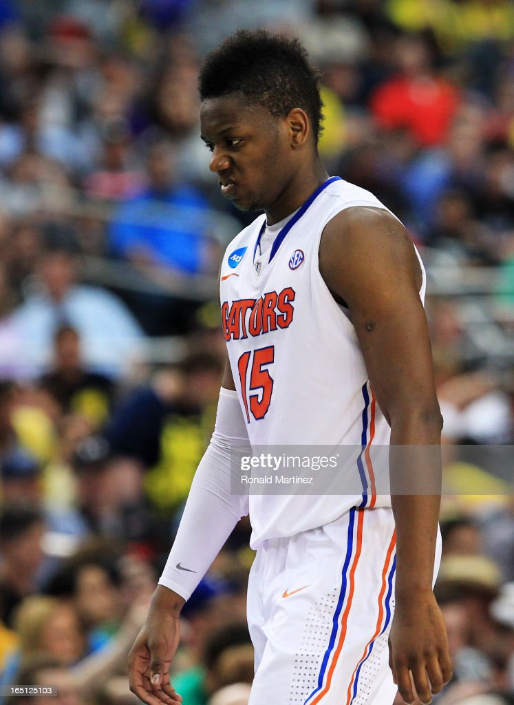 Will Yeguete #15 of the Florida Gators walks off of the court dejected after their 79 to 59 loss to the Michigan Wolverines during the South Regional Round Final of the 2013 NCAA Men's Basketball Tournament at Dallas Cowboys Stadium on March 31, 2013 in Arlington, Texas.