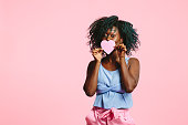 Portrait of a shy young woman  and holding a pink heart  and peeking over it, isolated on pink studio background