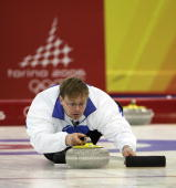 Wille Makela of Finland lines up the stone during the preliminary round of the men's curling between Sweden and Finland during Day 7 of the Turin...