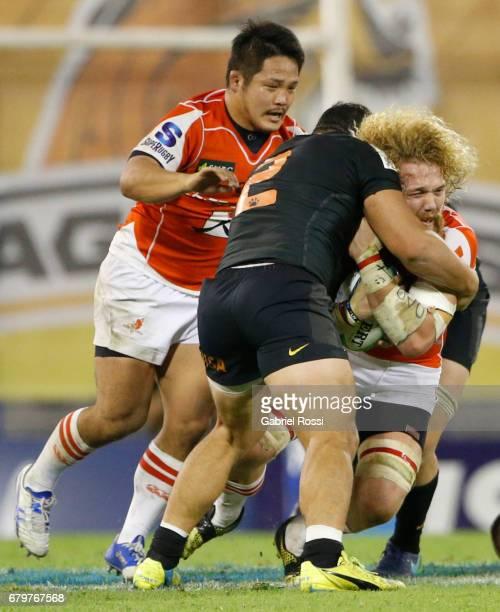 Willem Britz of Sunwolves is tackled by Agustin Creevy of Jaguares during the Super Rugby match between Jaguares and Sunwolves at Estadio Jose...