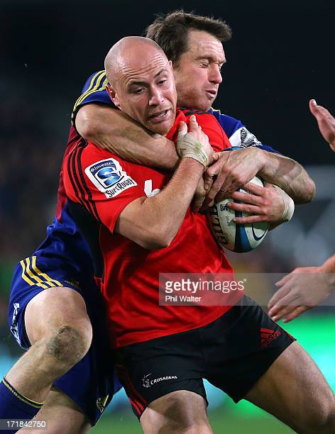 Willi Heinz of the Crusaders is tackled by Ben Smith of the Highlanders during the round 18 Super Rugby match between the Highlanders and the...