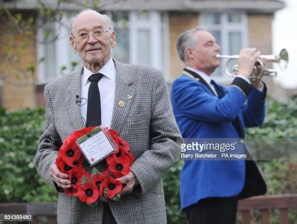Willi Schludecker holds a wreath alongside the 'Last Post' bugler Larry Coles