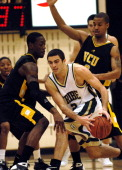 William and Mary guard David Schneider attempts to work out of a double team by Virginia Commonweath University's Larry Sanders and Eric Maynor...