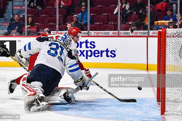 William Boysen of Team Denmark tips the puck past goaltender Veini Vehvilainen of Team Finland during the IIHF World Junior Championship preliminary...