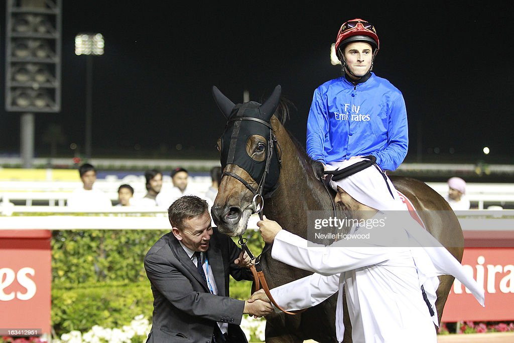 William Buick rides Sajjhaa (Blue Silks, red cap) in race 8, the 9f Group 1 Jebel Hatta race, and is led into the winner's circle by travelling head lad, <a gi-track='captionPersonalityLinkClicked' href=/galleries/search?phrase=Tommy+Burns&family=editorial&specificpeople=849163 ng-click='$event.stopPropagation()'>Tommy Burns</a> and Godolphin Trainer, Saeed bin Suroor, who are congratulating each other after an impressive win, during Super Saturday at Meydan Racecourse on March 9, 2013 in Dubai, United Arab Emirates.