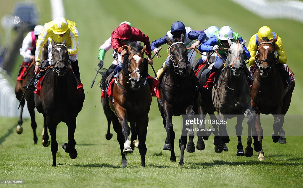 William Buick riding Feel Like Dancing (C, red) to win The Bahrain Trophy at Newmarket racecourse on July 11, 2013 in Newmarket, England.