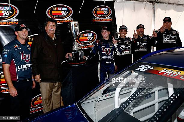 William Byron driver of the Liberty University Chevrolet right of trophy poses with Vice Chairman of NASCAR Mike Helton left of trophy and his team...