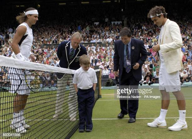 William Caines sevenyearsold from Beckenham Kent represents Cancer Research UK as he performs the coin toss ahead of the Men's singles final match...