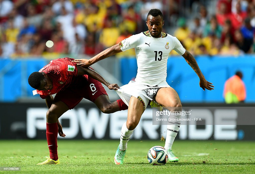 William Carvalho of Portugal and Jordan Ayew of Ghana compete for the ball during the 2014 FIFA World Cup Brazil Group G match between Portugal and...