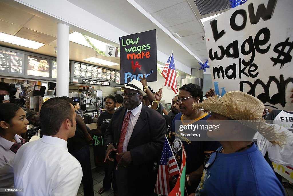 William D. Smart, Jr., pastor of the Southern Christian Leadership Conference, center, protests with fast-food workers and supporters organized by the Service Employees International Union (SEIU) inside of a McDonald's Corp. restaurant in Los Angeles, California, U.S., on Thursday, Aug. 29, 2013. Fast-food workers in 50 U.S. cities plan to walk off the job today, ratcheting up pressure on the industry to raise wages and demanding the right to wages of $15 an hour, more than double the federal minimum of $7.25. Photographer: Patrick T. Fallon/Bloomberg via Getty Images
