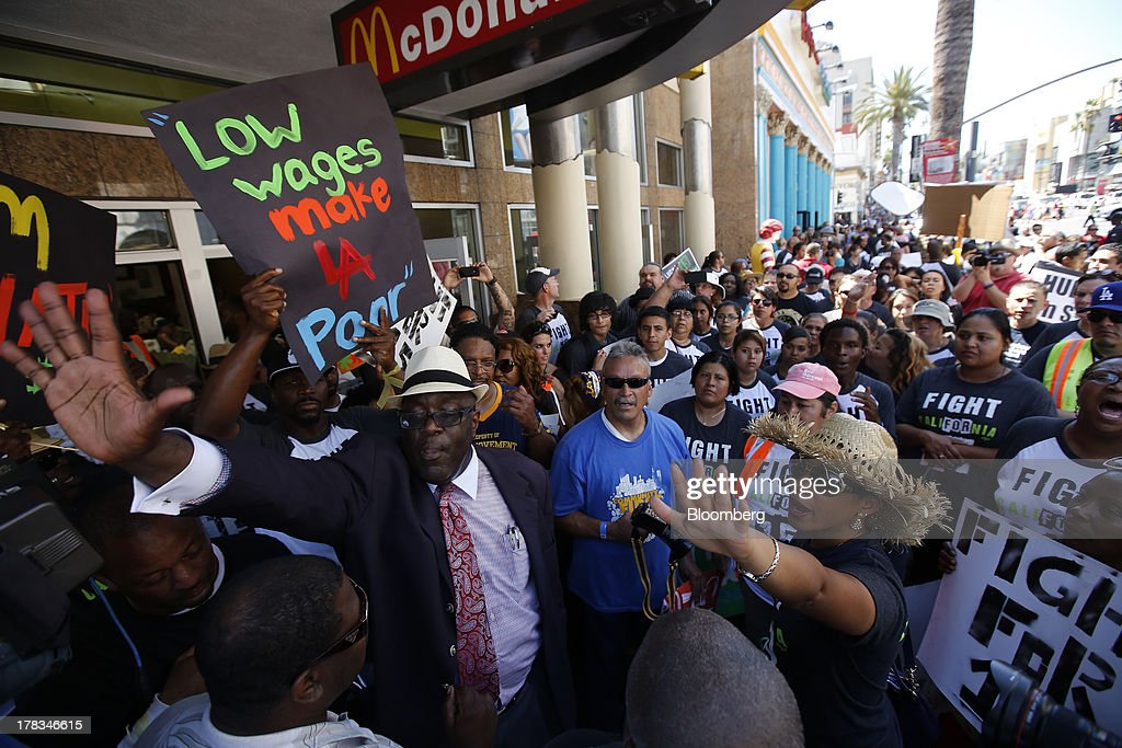 William D. Smart Jr., pastor of the Southern Christian Leadership Conference, center, protests with fast-food workers and supporters organized by the Service Employees International Union (SEIU) outside of a McDonald's Corp. restaurant in Los Angeles, California, U.S., on Thursday, Aug. 29, 2013. Fast-food workers in 50 U.S. cities plan to walk off the job today, ratcheting up pressure on the industry to raise wages and demanding the right to wages of $15 an hour, more than double the federal minimum of $7.25. Photographer: Patrick T. Fallon/Bloomberg via Getty Images
