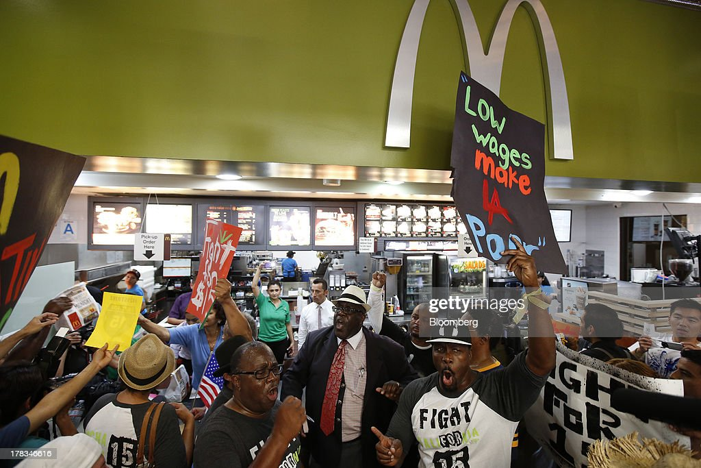 William D. Smart Jr., pastor of the Southern Christian Leadership Conference, center, protests with fast-food workers and supporters organized by the Service Employees International Union (SEIU) inside of a McDonald's Corp. restaurant in Los Angeles, California, U.S., on Thursday, Aug. 29, 2013. Fast-food workers in 50 U.S. cities plan to walk off the job today, ratcheting up pressure on the industry to raise wages and demanding the right to wages of $15 an hour, more than double the federal minimum of $7.25. Photographer: Patrick T. Fallon/Bloomberg via Getty Images