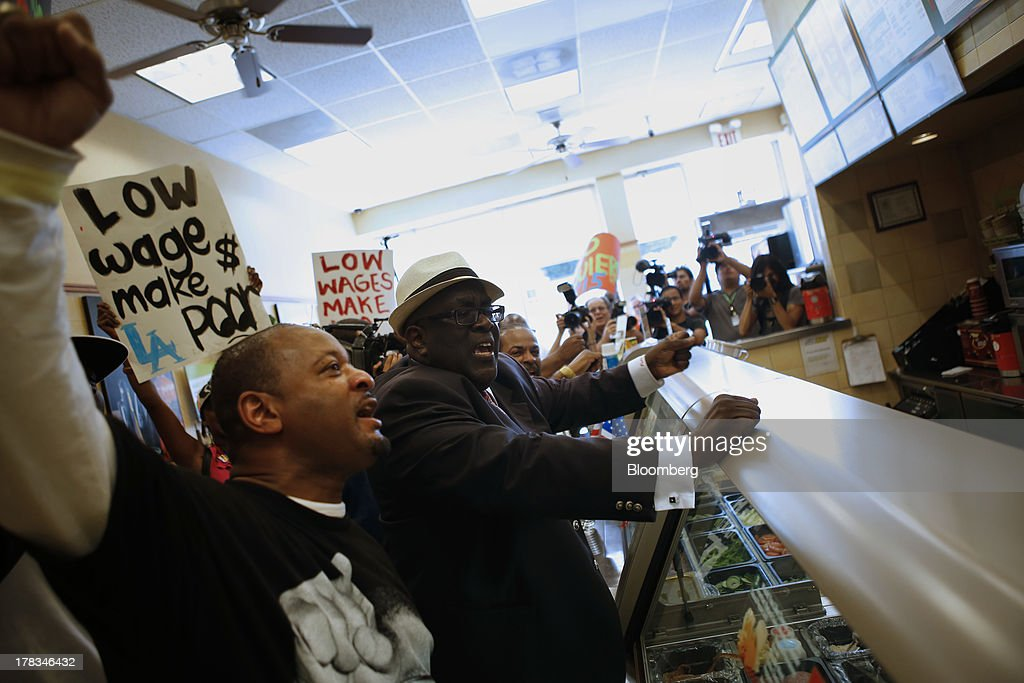 William D. Smart, Jr., pastor of the Southern Christian Leadership Conference, right, protests with Fast-food workers and supporters organized by the Service Employees International Union (SEIU) inside of a Subway restaurant in Los Angeles, California, U.S., on Thursday, Aug. 29, 2013. Fast-food workers in 50 U.S. cities plan to walk off the job today, ratcheting up pressure on the industry to raise wages and demanding the right to wages of $15 an hour, more than double the federal minimum of $7.25. Photographer: Patrick T. Fallon/Bloomberg via Getty Images