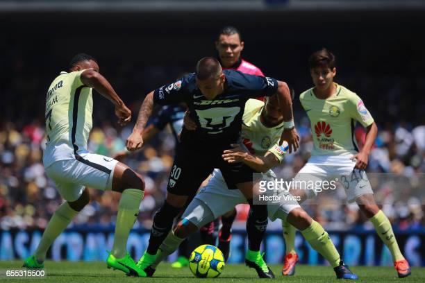 William Da Silva and Jose Guerrero of America struggles for the ball with Nicolas Castillo of Pumas during the 11th round match between Pumas UNAM...