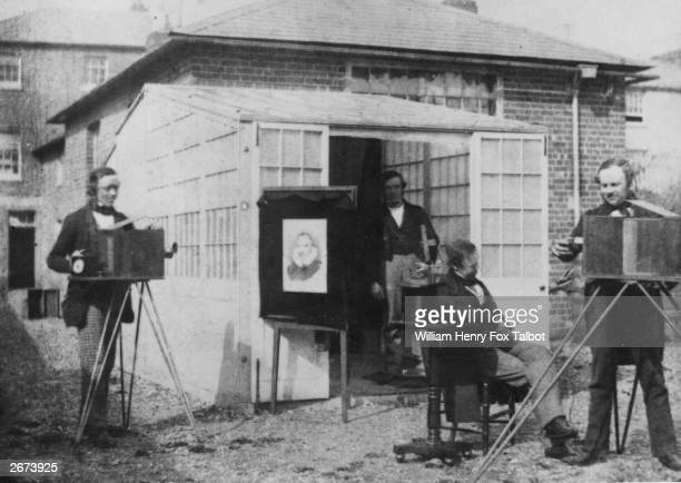 William Henry Fox Talbot considered to be the true inventor of photography at his studio near Reading Fox Talbot right is adjusting the lens on a...