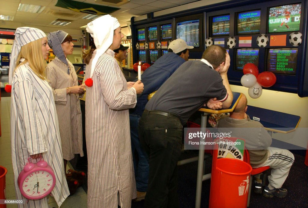 William Hill betting shop staff in London,join customers to watch England's early morning World Cup kick off against Nigeria in the team's final group one match, in Sapporro, Japan, after opening up in their nightclothes at 7.00am.