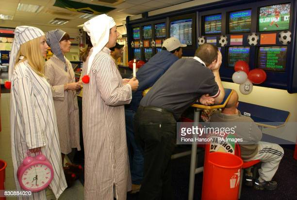 William Hill betting shop staff in Londonjoin customers to watch England's early morning World Cup kick off against Nigeria in the team's final group...