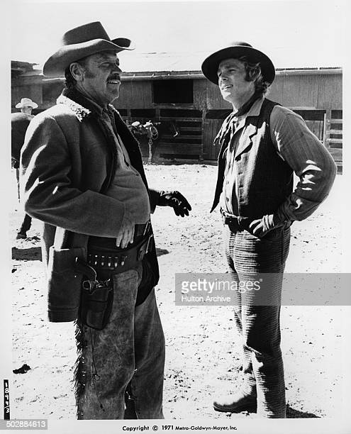 William Holden and Ryan O'Neal share a joke in a scene for the the MGM movie 'Wild Rovers' circa 1971