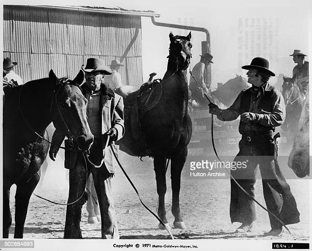 William Holden and Ryan O'Neal work on the RBar Ranch in a scene for the the MGM movie 'Wild Rovers' circa 1971