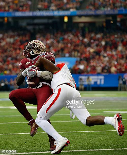 William Jackson III of the Houston Cougars tackles Derwin James of the Florida State Seminoles in the first quarter during the ChickfilA Peach Bowl...