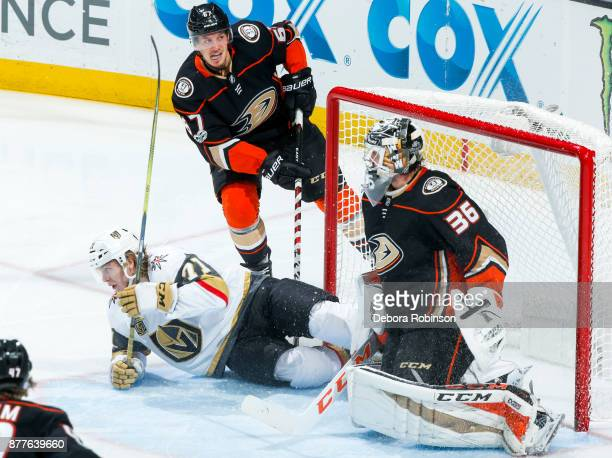 William Karlsson of the Vegas Golden Knights falls to the ice in the goal as Rickard Rakell and goalie John Gibson of the Anaheim Ducks look on...