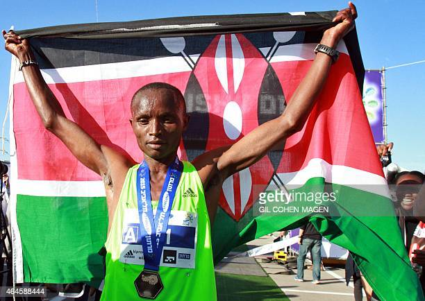 William Kiprono from Kenya raises his national flag as he celebrates winning the 2015 Tel Aviv Marathon on February 27 2015 in the Mediterranean...