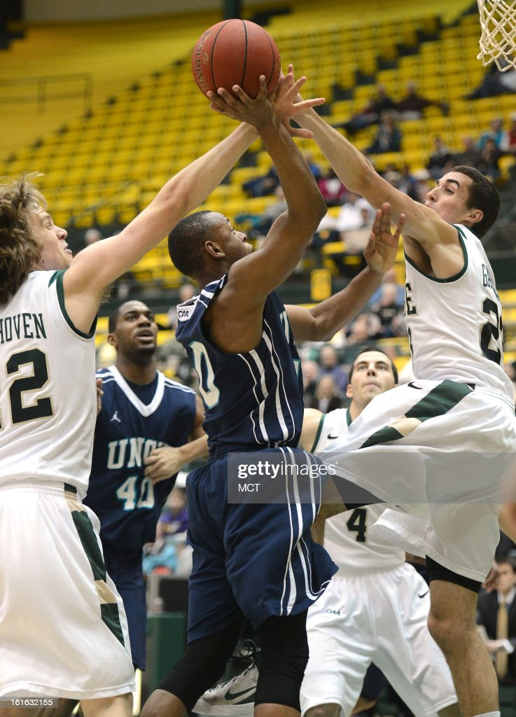 William & Mary forward Tim Rusthoven (22), left, and William & Mary forward Kyle Gaillard (23) defend a shot attempt by North Carolina-Wilmington forward Cedrick Williams (40) in the first half at Kaplan Arena in Williamsburg, Virginia, Wednesday, February 13, 2013.