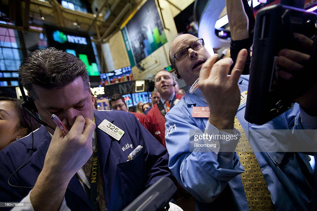 William McInerney, a trader with Blue Point Securities LLC, left, works on the floor of the New York Stock Exchange (NYSE) in New York, U.S., on Friday, Feb. 1, 2013. U.S. stocks rallied, briefly sending the Dow Jones Industrial Average above 14,000, as data showed hiring increased in January after accelerating more than previously estimated at the end of 2012 and manufacturing grew. Photographer: Jin Lee/Bloomberg via Getty Images
