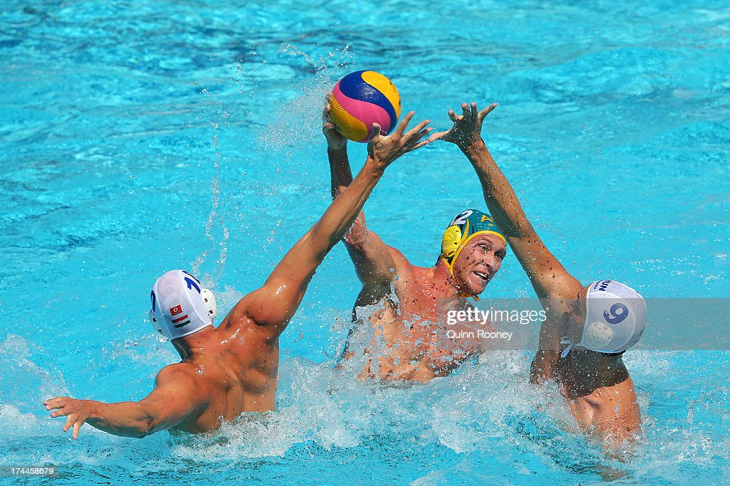 William Miller of Australia (C) looks to offload the ball despite the challenge of Denes Varga (L) and Daniel Varga (R) of Hungary during the Men's Water Polo first preliminary round match between Hungary and Australia on day seven of the 15th FINA World Championships at the Piscina Bernat Picornell on July 26, 2013 in Barcelona, Spain.