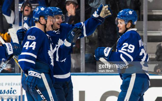William Nylander of the Toronto Maple Leafs celebrates his empty net goal with Morgan Rielly and Zach Hyman against the Boston Bruins during the...