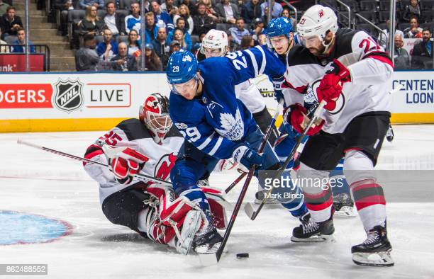 William Nylander of the Toronto Maple Leafs goes to the net against Cory Schneider and Kyle Palmieri of the New Jersey Devils during the third period...