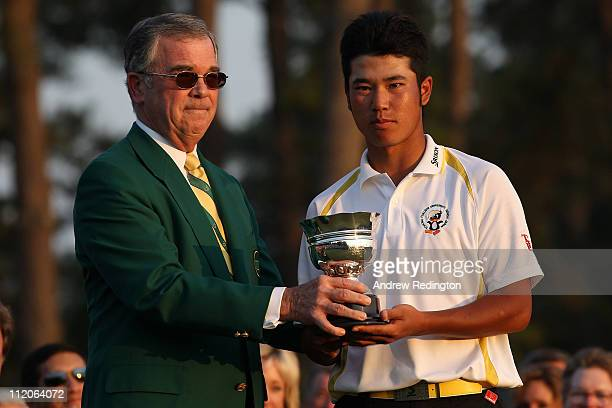 William Porter Payne presents a trophy to the leading amateur Hideki Matsuyama of Japan during the final round of the 2011 Masters Tournament on...