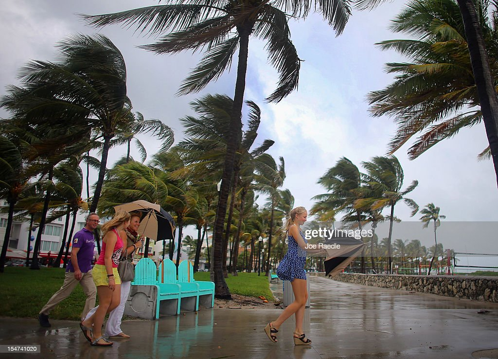 William Rath, Julie Rath, Laura Rath and Weera Rath, on vacation from the Netherlands, walk to the beach as they are buffeted by high winds of the outer bands of Hurricane Sandy on October 25, 2012 in Miami Beach, Florida. After passing over Jamaica Hurricane Sandy is expected to hit eastern Cuba and head into the Bahamas today and tomorrow. There is a tropical storm warning in place for coastal Miami-Dade, Broward, and Palm Beach Counties and the Atlantic waters off southeast Florida.