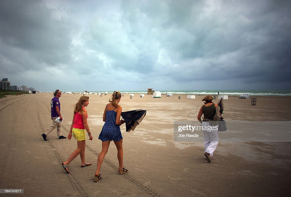 William Rath, Julie Rath, Weera Rath and Laura Rath, on vacation from the Netherlands, walk on the beach as they are buffeted by high winds of the outer bands of Hurricane Sandy on October 25, 2012 in Miami Beach, Florida. After passing over Jamaica Hurricane Sandy is expected to hit eastern Cuba and head into the Bahamas today and tomorrow. There is a tropical storm warning in place for coastal Miami-Dade, Broward, and Palm Beach Counties and the Atlantic waters off southeast Florida.