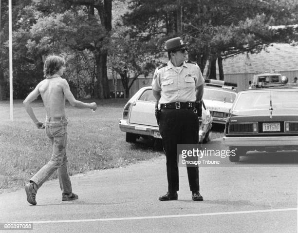 William Rouse son of slain Libertyville Ill couple Bruce and Darlene Rouse walks near a policemen as investigators seek clues on June 6 1980
